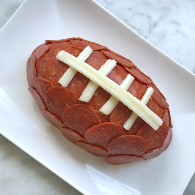 super easy football party food ideas - football cheese ball with pepperoni and string cheese