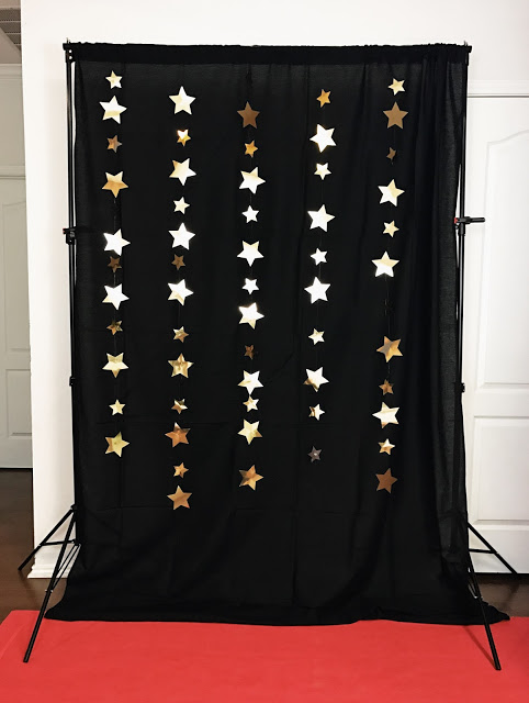 hollywood movie party decor - black photo backdrop with gold star garlands